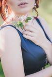 有红色头发的年轻美丽的妇女在摆在一个开花的庭院里的一件蓝色礼服 免版税库存图片