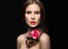 有红色嘴唇和一朵玫瑰的美丽的女孩在她的头发 秀丽表面 免版税库存照片