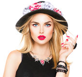 有红色嘴唇和修指甲的性感的白肤金发的妇女在现代黑帽会议 免版税库存图片