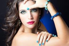 有红色嘴唇和蓝色钉子的性感的秀丽女孩 免版税库存照片