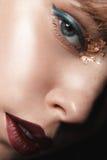 有红色嘴唇和金子的性感的白肤金发的女孩在一件黑暗的外套的眼睛 免版税库存照片