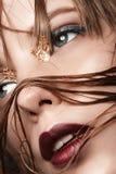 有红色嘴唇和金子的性感的白肤金发的女孩在一件黑暗的外套的眼睛 免版税库存图片