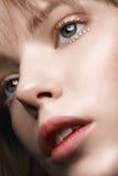 有红色嘴唇和金子的性感的白肤金发的女孩在一件黑暗的外套的眼睛 免版税图库摄影