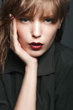 有红色嘴唇和金子的性感的白肤金发的女孩在一件黑暗的外套的眼睛 库存图片