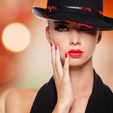 有红色嘴唇和钉子的美丽的妇女在黑帽会议 免版税图库摄影