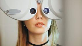 有红色嘴唇的可爱的女孩检查在现代设备的眼睛在医疗中心,远距照相 库存图片