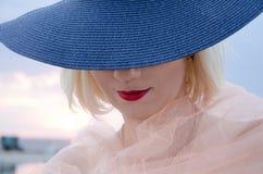 有红色嘴唇的少妇在日落的一个帽子 免版税库存照片