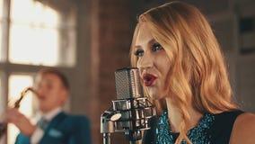 有红色嘴唇的歌手在阶段执行在话筒 减速火箭的样式 萨克斯管吹奏者 股票视频
