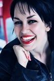 有红色嘴唇的深色的妇女咬住舌头的 库存照片