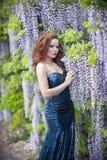 有红色嘴唇的美丽的少妇在sprakling的蓝色礼服 库存图片