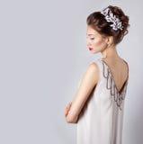 有红色嘴唇的美丽的年轻性感的典雅的愉快的微笑的妇女,与白花的美好的时髦的发型在她的头发 库存图片