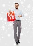 有红色购物袋的微笑的人在雪 免版税库存照片