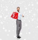 有红色购物袋的微笑的人在雪 图库摄影
