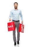 有红色购物袋的微笑的人 免版税库存图片