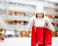 有红色购物袋的微笑的少妇 库存照片