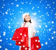 有红色购物袋的微笑的少妇 免版税库存照片
