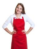 有红色围裙和横渡的胳膊的常设女服务员 免版税图库摄影