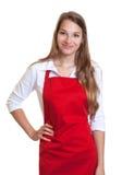有红色围裙的微笑的女服务员 免版税库存图片