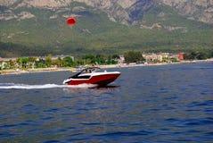 有红色parashute的红色快艇 库存照片