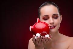 有红色piggybank的少妇 免版税库存照片