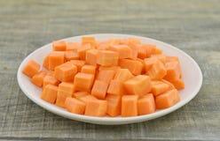有红萝卜裁减立方体的白色板材在木的,土气 库存照片