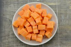 有红萝卜裁减立方体的白色板材在木的,土气 库存图片