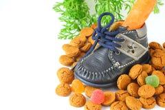 有红萝卜voor的Sinterklaas儿童的鞋子和pepernoten 免版税库存图片