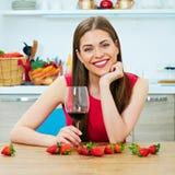 有红葡萄酒玻璃的微笑的少妇 免版税图库摄影