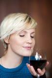 有红葡萄酒玻璃的年轻白肤金发的妇女 库存图片