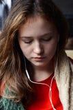 有红褐色的头发的女孩听到与他的眼睛的音乐的关闭了 图库摄影