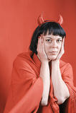 有红魔垫铁的俏丽的深色的妇女 免版税库存照片