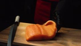 有红鲑鱼片断的特写镜头厨师  黑围裙和手套的专业厨师在木板上把三文鱼放片断  股票录像