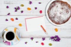 有纸、铅笔、茶杯和蛋糕的女性桌面 免版税库存图片