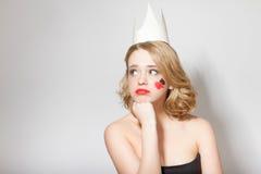 有纸冠的美丽的年轻式样女孩在她的头,有心脏和锹的在她的面孔 免版税库存图片