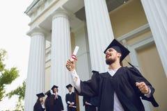 有纸卷的人微笑着以大学毕业生为背景 库存照片
