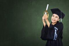 有纸卷的愉快的研究生女孩 免版税库存照片