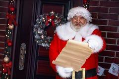 有纸卷纸的微笑的圣诞老人 库存图片
