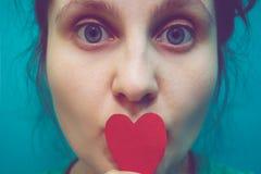 有纸心脏的女孩在减速火箭的颜色 免版税库存照片