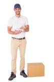 有纸板箱和剪贴板的愉快的送货人 库存照片
