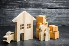 有纸板箱的人们是在房子附近 物产和物品,送货上门的运输 在线购物 乔迁庆宴 免版税库存照片