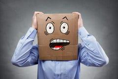 有纸板箱的人在他的显示震惊和惊奇的表示的头 库存图片