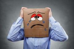 有纸板箱的人在他的显示哀伤的表示的头 免版税库存照片