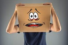 有纸板箱的人在他的头和害怕的神色skethed 免版税图库摄影