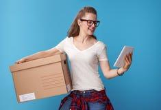 有纸板箱的微笑的行家使用在蓝色的片剂个人计算机 免版税库存照片