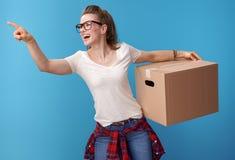 有纸板箱的愉快的妇女指向某事的在蓝色 图库摄影