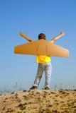 有纸板箱的愉快的男孩反对飞行天空梦想的翼  免版税库存图片