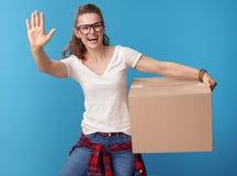 有纸板箱问候的微笑的少妇在蓝色 免版税库存图片