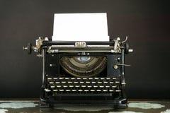 有纸片的老和多灰尘的打字机 免版税库存图片