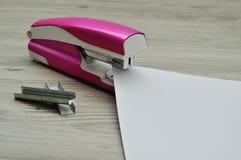 有纸的一台桃红色订书机和堆订书机 图库摄影