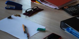 有纸的一张书桌书写电话计算器玻璃 免版税库存照片